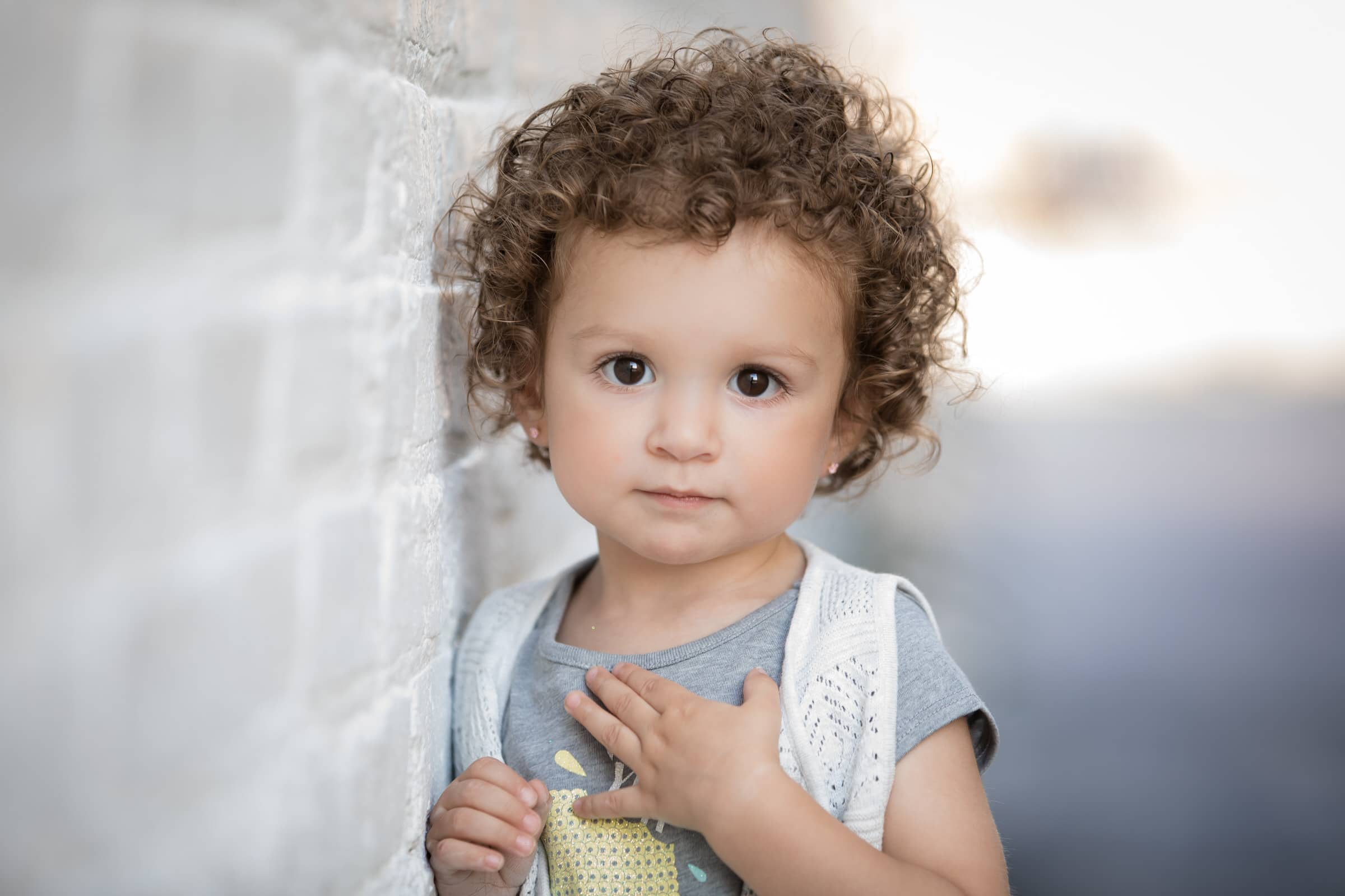 child model with curly hair and brown eyes